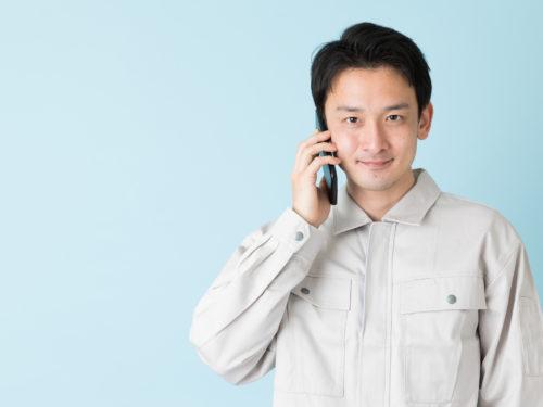 電話対応をする作業服の男性