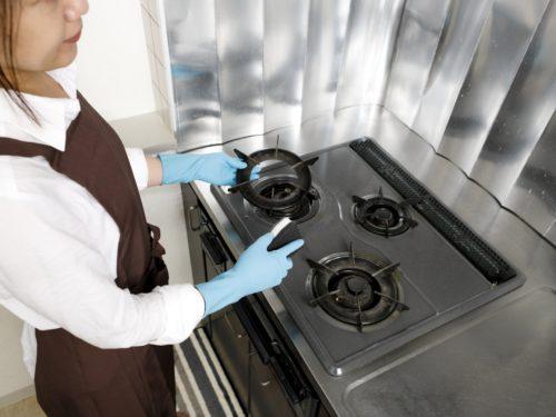 油汚れを掃除する女性